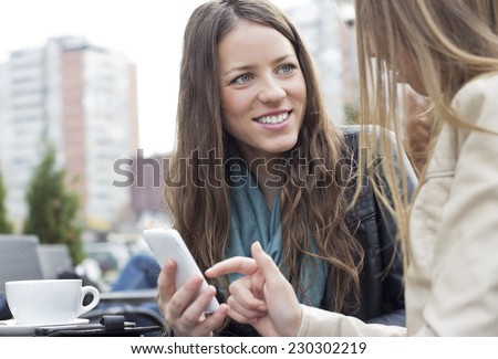 Young happiness woman sitting in the cafe and using a  smart phone outdoors. - stock photo