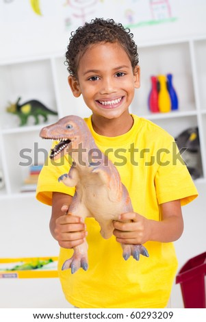 young happy african american boy playing with dinosaur