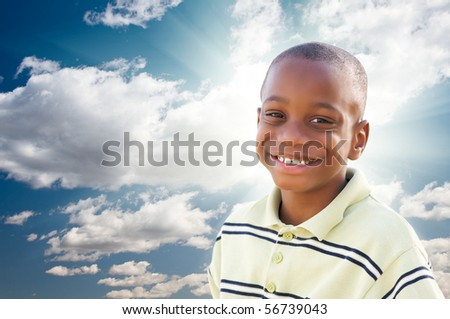 Young Happy African American Boy with Dramatic Clouds and Sky and Sun Rays. - stock photo
