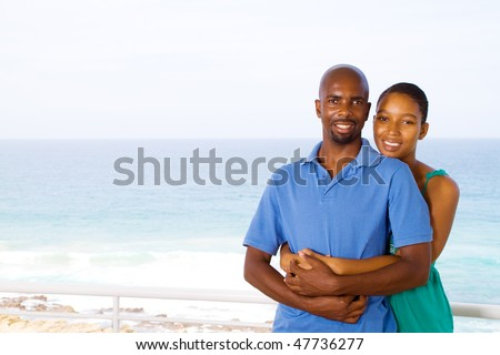 young happy african american couple hugging, background is beautiful ocean view