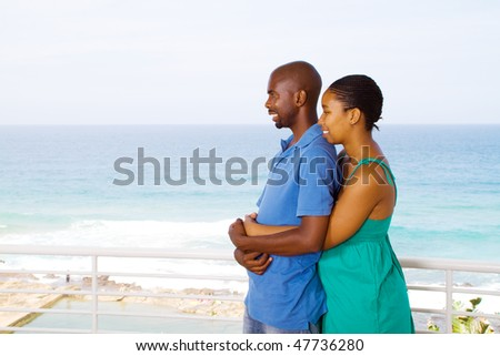 young happy african american couple hugging, background is beautiful sea view