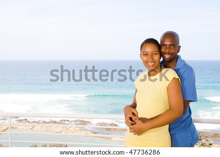 young happy african american couple hugging on balcony