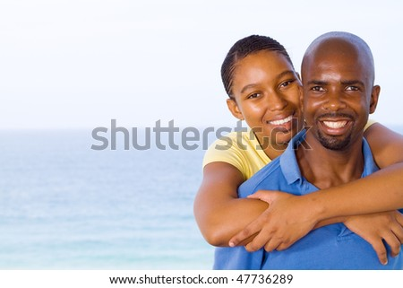 young happy african american couple piggyback, background is beautiful sea view - stock photo