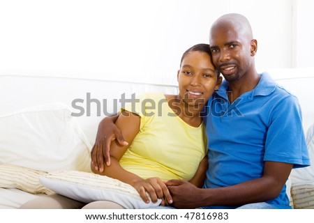 young happy african american couple relaxing at home on sofa - stock photo