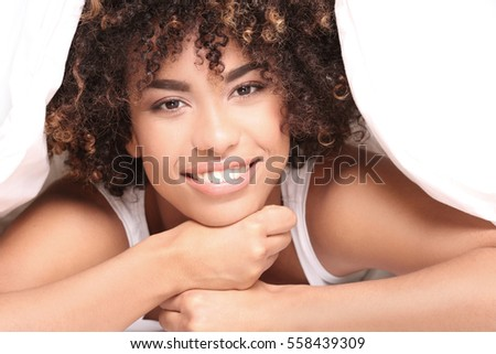 Young happy african american girl with afro lying in bed, relaxing, smiling to the camera.