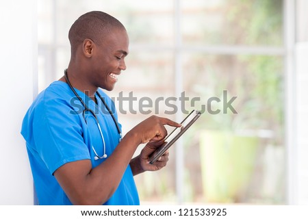young happy african american medical worker using tablet computer - stock photo