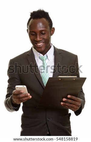 Young happy African businessman smiling and using mobile phone while holding clipboard isolated against white background