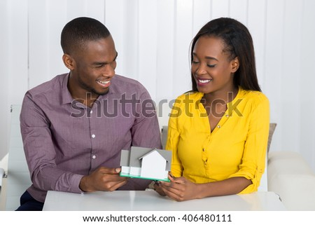Young Happy African Couple Holding A House Model At Home