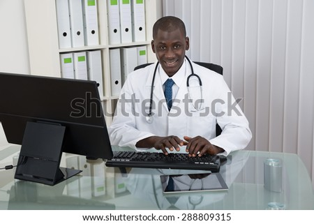 Young Happy African Doctor Working On Computer At Desk - stock photo