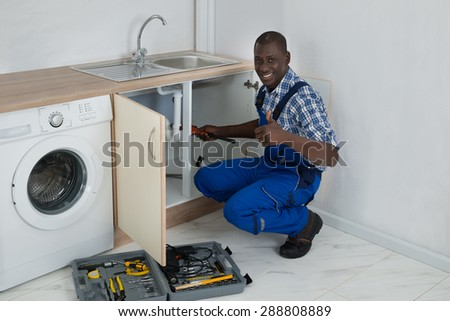 Young Happy African Male Plumber Fixing Sink In Kitchen - stock photo