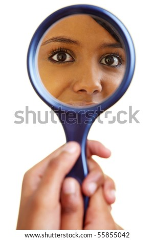 Young happy african woman looking into a mirror