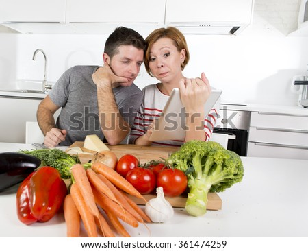 young happy American couple working in domestic kitchen together wife following recipe in digital pad working with her husband preparing vegetable dish in healthy nutrition concept - stock photo