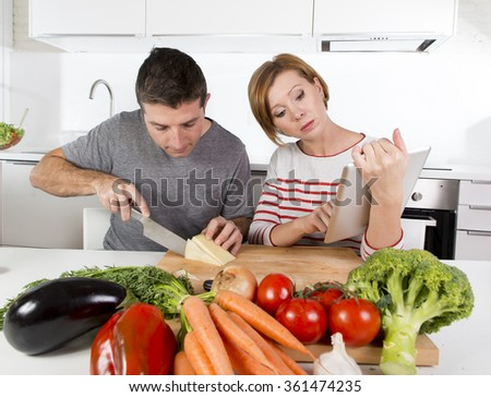 young happy American couple working in domestic kitchen together wife following recipe with digital pad husband slicing cheese preparing vegetable dish in healthy nutrition concept - stock photo