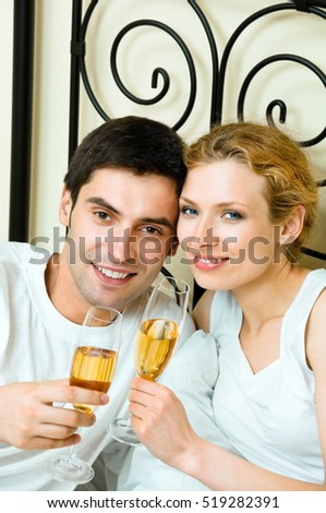 Young happy amorous couple celebrating with champagne at bedroom. Love, relations, holidays, romantic concept shot.