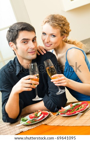 Young happy amorous couple celebrating with champagne at home - stock photo