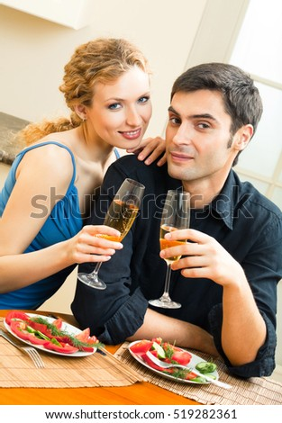 Young happy amorous couple celebrating with champagne at home. Love, relations, romantic concept shot.