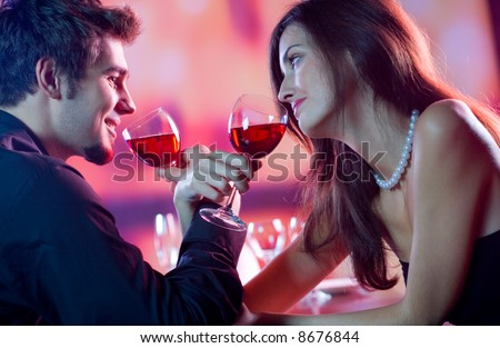 Young happy amorous couple celebrating with red wine at restaurant - stock photo