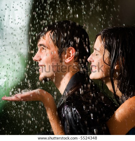 Young happy amorous couple hugging under a rain - stock photo