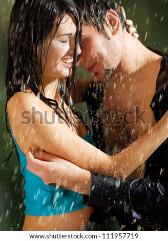 Young happy amorous couple hugging under a rain, outdoors - stock photo