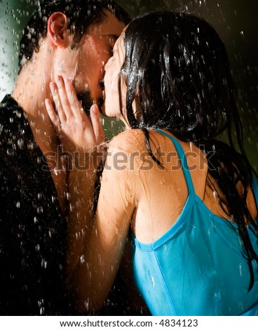 Young happy amorous couple kissing and hugging under a rain