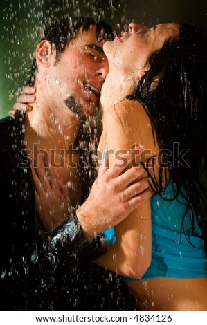 Young happy amorous couple kissing and hugging under a rain - stock photo