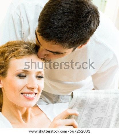 Young happy amorous couple reading newspaper at home