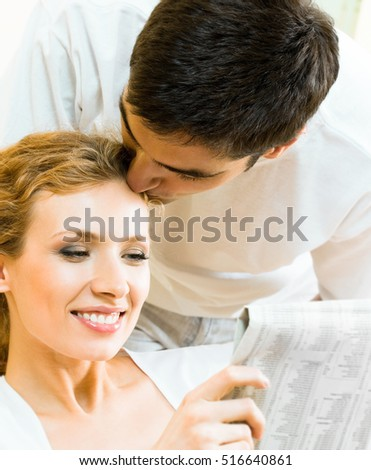 Young happy amorous couple reading newspaper at home. Love, relations, romantic concept shoot.