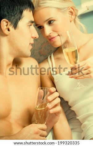 Young happy amorous couple with champagne at bedroom - stock photo