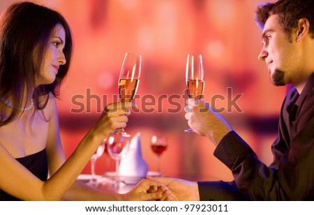 Young happy amorous couple with glasses of champagne on romantic date at restaurant - stock photo