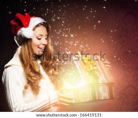 Young, happy and emotional teenage girl opening the magical Christmas present box - stock photo