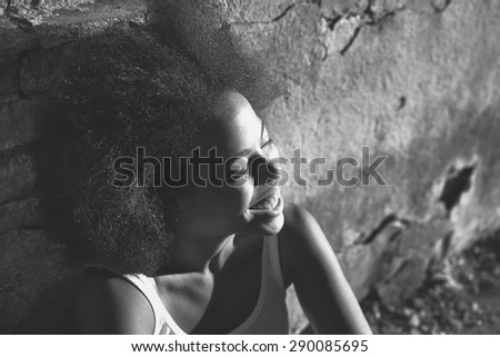 young happy and  pretty curly afro woman laughing and sitting near old wall. black and white picture - stock photo