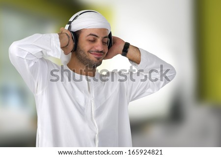 Young happy Arabian man with headphones listening to music  - stock photo