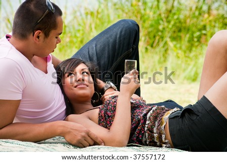Young happy asian couple enjoying their time outdoors - stock photo