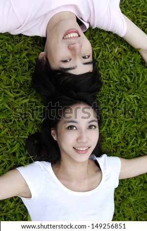 Young happy asian couple laying on grass - stock photo