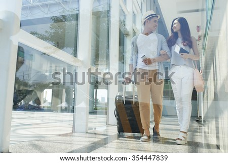 Young happy Asian couple with luggage walking in the airport - stock photo