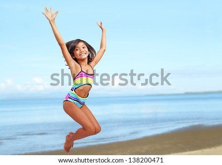 Young happy asian girl jumping at the beach. - stock photo