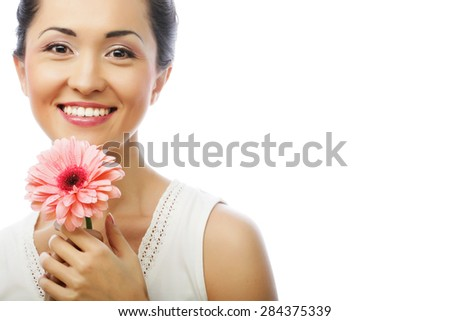 Young happy asian woman holding a pink gerbera, isolated on white - stock photo