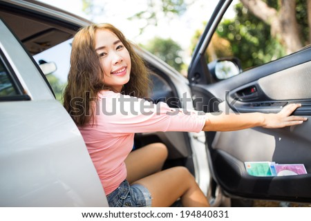 young happy asian woman in car ready for vacation - stock photo