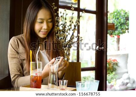 Young happy asian woman looking  at her cellphoneand texting message in the restaurant - stock photo