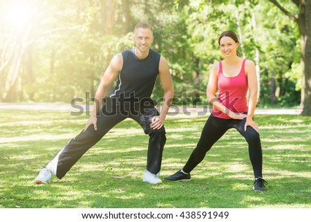 Young Happy Athletic Couple Doing Exercise In Park