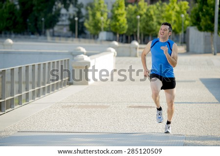 young happy athletic man with sunglasses practicing running on urban city park background in summer sport training session, body and health care and healthy lifestyle concept