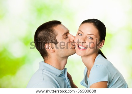 Young happy attractive couple, outdoors - stock photo