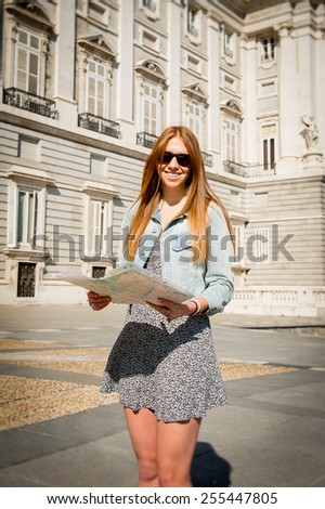 young happy attractive exchange student girl having fun in town visiting Madrid city reading tourist map having fun outdoors in tourism and travel vacation concept - stock photo