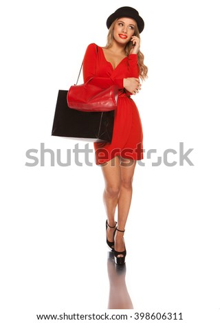 Young happy attractive female in red dress speaking over the mobile phone , on white,