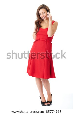 Young happy attractive female in red dress text using her mobile phone, shoot over white background - stock photo