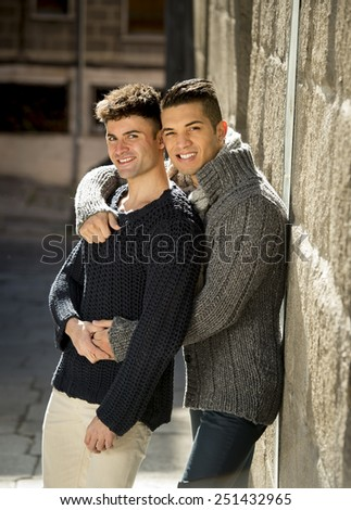 young happy attractive gay men couple hugging and posing outdoors on street in sexual freedom and free homosexual love concept in urban background - stock photo