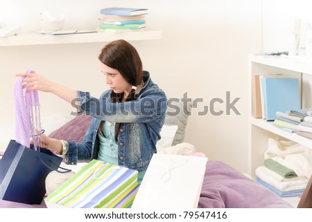 Young happy attractive girl unpack shopping bags in student apartment