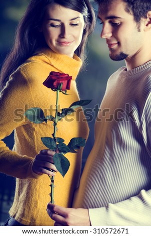 Young happy attractive smiling couple with rose on romantic date - stock photo