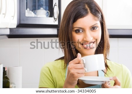 young happy attractive woman drinking coffee in kitchen - stock photo