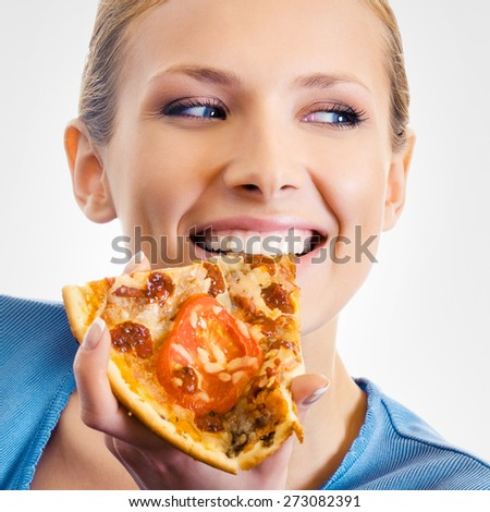 Young happy attractive woman eating pizza,  over grey background